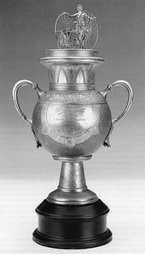Tricycle Cup Trophy<br> First Prize, September 9, 1885<br> Springfield, Massachusetts<br> Height: 23&quot;<br> Silver plated<br> United States